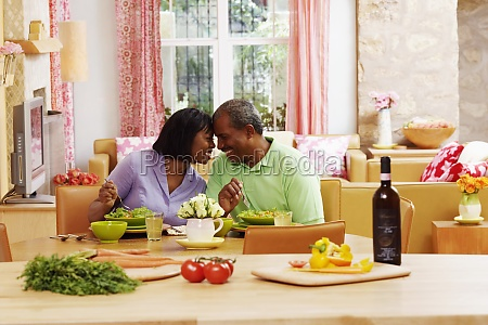 mature couple eating salad and looking