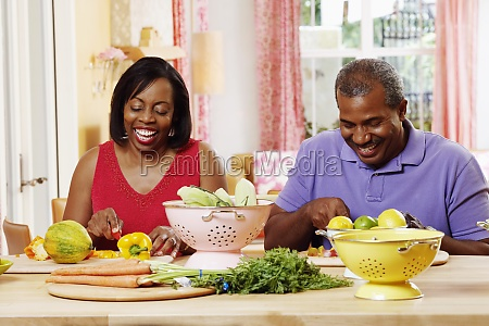 mature couple cutting vegetables and smiling