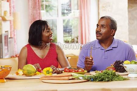 mature couple cutting vegetables and talking