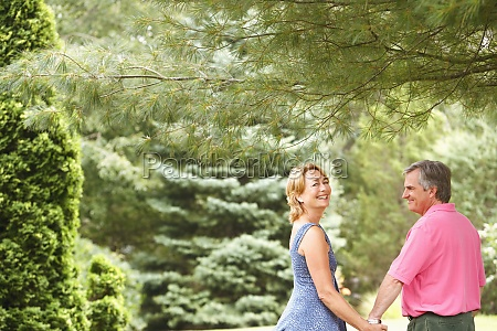 mature couple holding hands and smiling