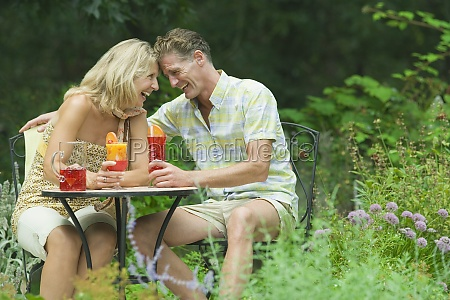 mature couple holding glasses of juice