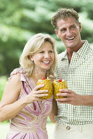 mature couple holding pineapples and smiling