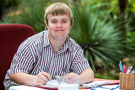 boy with down syndrome at desk