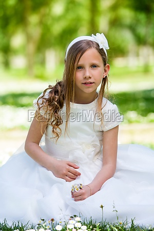 girl in communion dress holding flowers