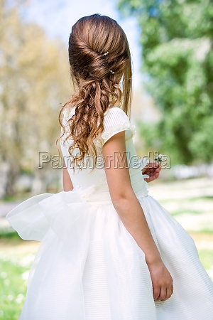 girl in communion dress showing hairstyle