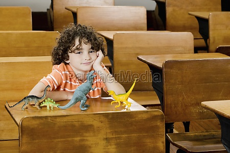 schoolboy sitting with toys in a