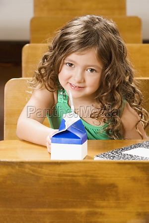 schoolgirl sitting with a juice packet