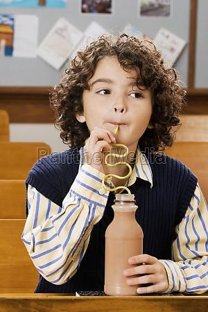 schoolboy drinking chocolate milkshake in a