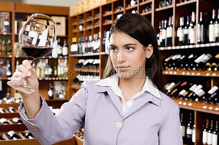 businesswoman examining a glass of red