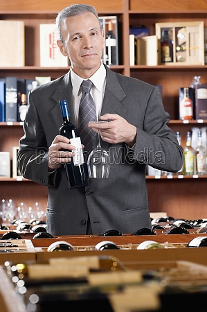 businessman holding a wine bottle and