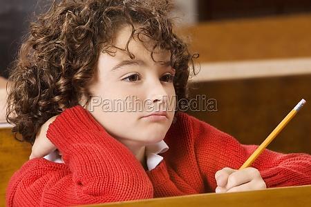 schoolboy thinking in a classroom