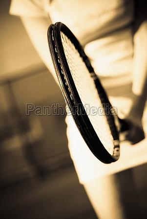 womanZs hand holding a tennis racket