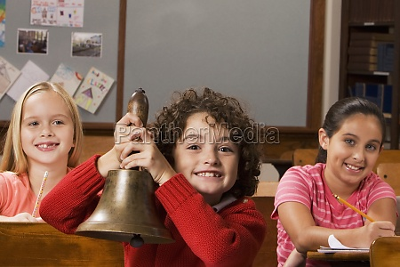 schoolboy holding a bell with two