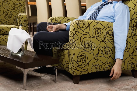 drunk businessman sitting in an armchair