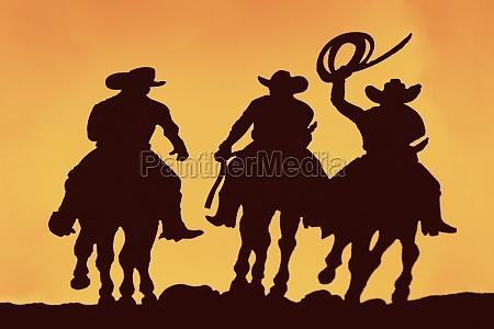 silhouette of three men horseback riding