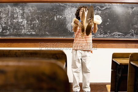 schoolboy playing cymbals in a classroom