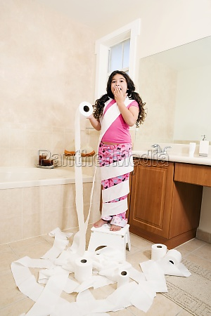 girl playing with toilet paper rolls