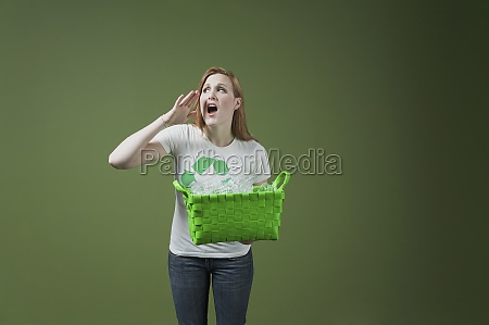 woman holding a recycling bin and