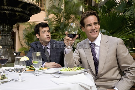 two businessmen having lunch in a