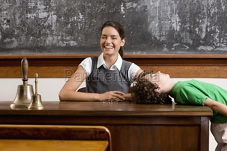 schoolboy bending backward on a table