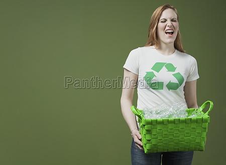 woman holding a recycling bin