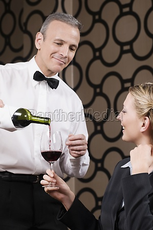waiter pouring red wine into a