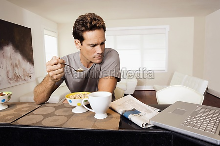 man having breakfast and reading a