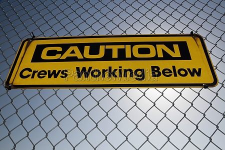 caution sign on a chainlink fence