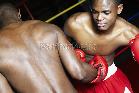 two male boxers fighting in a