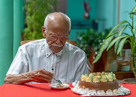 old man eating cake