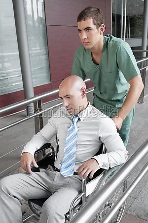 male nurse pushing a man in