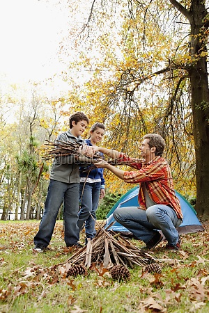 man with his children collecting firewood
