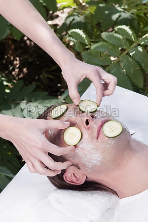 beautician putting cucumber slices on a