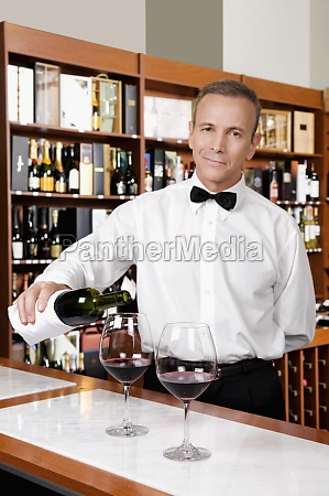 waiter pouring red wine into wine