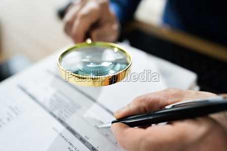fraud detective using magnifying glass