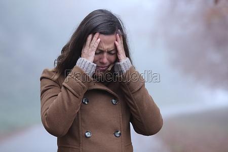 sad woman in winter complaining alone