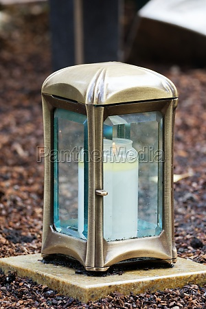 brass grave lantern with burning candle
