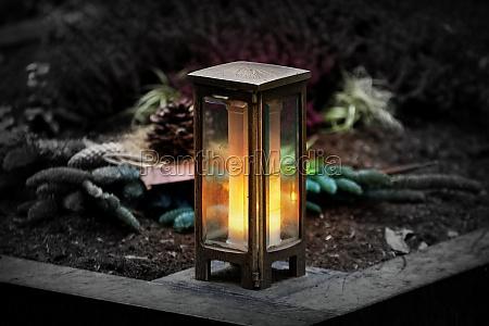 metal grave lantern with burning candle