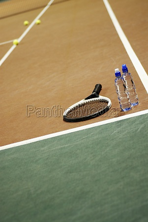 tennis racket with two water bottles