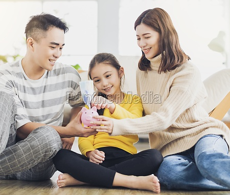 father mother and daughter holding a