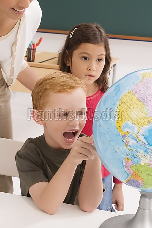 schoolboy looking at a globe and