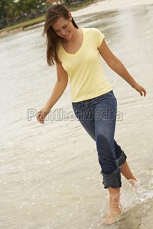 teenage girl walking in water
