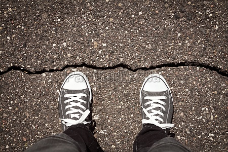 man standing on cracked asphalt floor