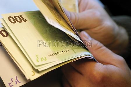 businessman holding several one hundred euro