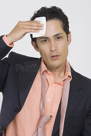 portrait of a businessman wiping sweat