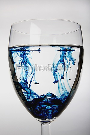 blue substance dissolving in a glass