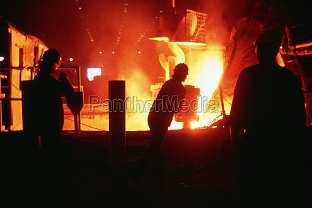 silhouettes of steel workers working in