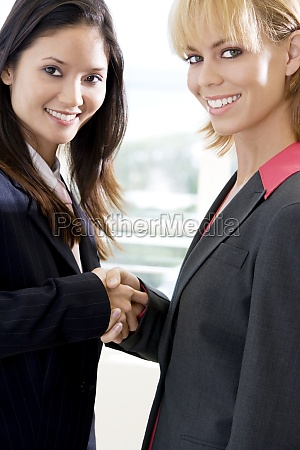 portrait of two businesswomen shaking hands