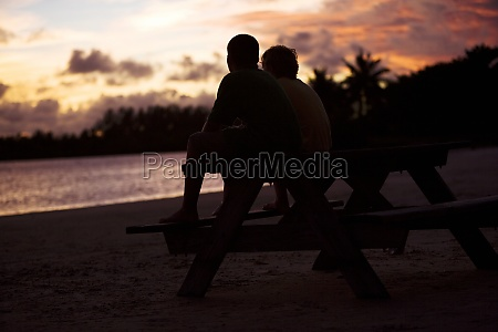 silhouette of two boys sitting on