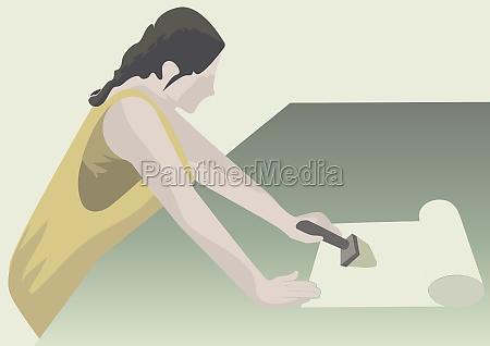 woman applying wallpaper glue on a